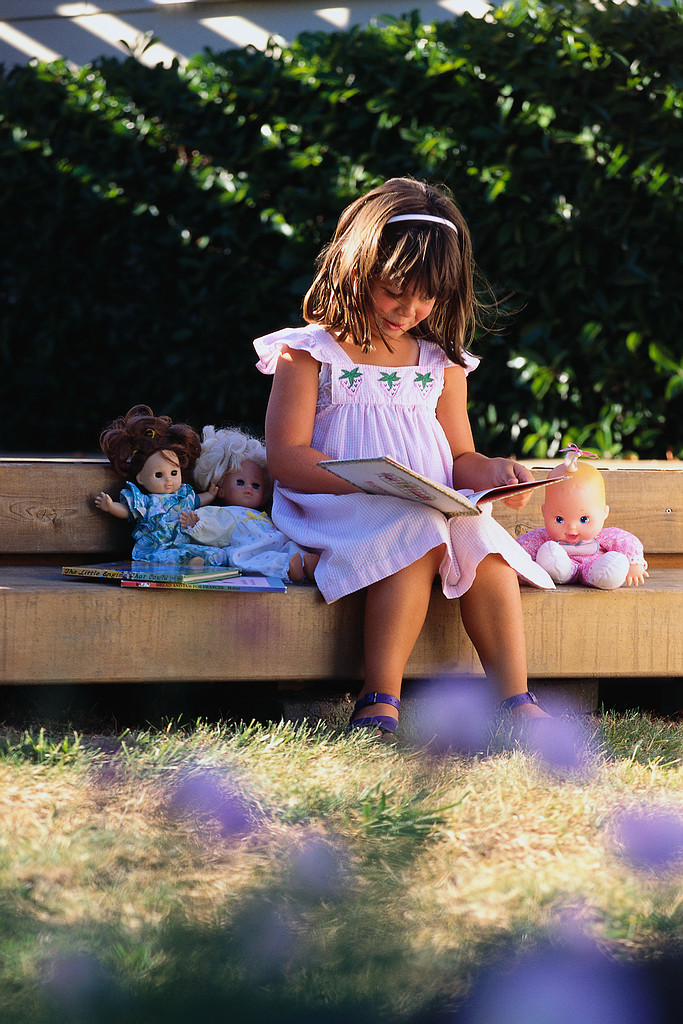 Little Girl Reading in Backyard